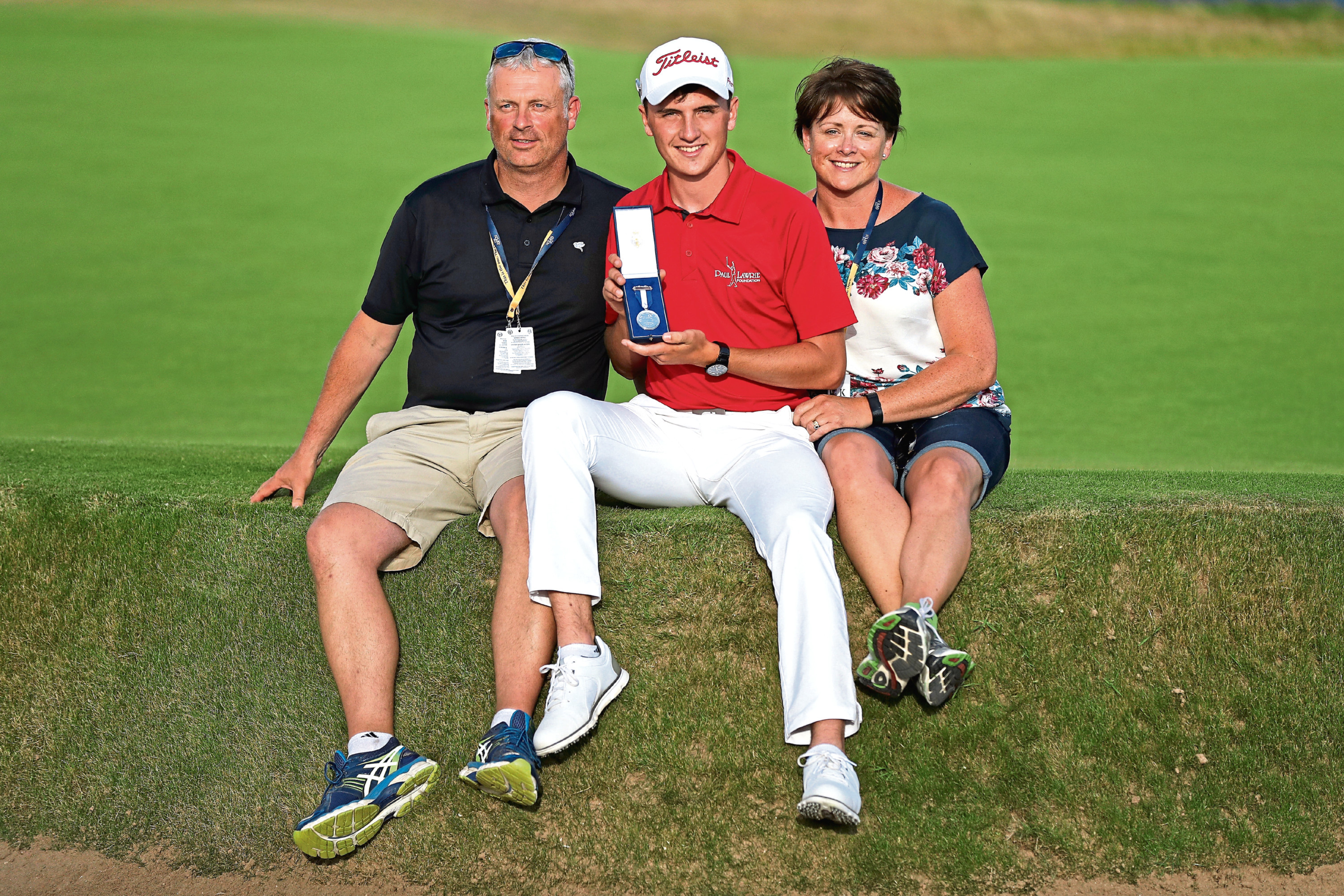 Sam Locke of Scotland holds the Silver Medal awarded to highest placed amateur with his parents Andrew and Vicky after the final round of the 147th Open Championship at Carnoustie