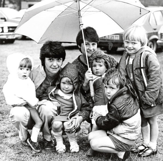 Julia Duguid, left, with her children Michelle, 2, and Louise, 3, share an umbrella with Anne Ogston and her youngsters Sarah, 2, Steven, 4, and Lynne, 5, at the show