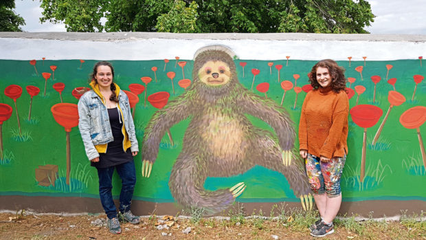 Leila Kleineidam, left,  and Claire Kidd with their 32 metre-long mural in Eric Hendrie Park