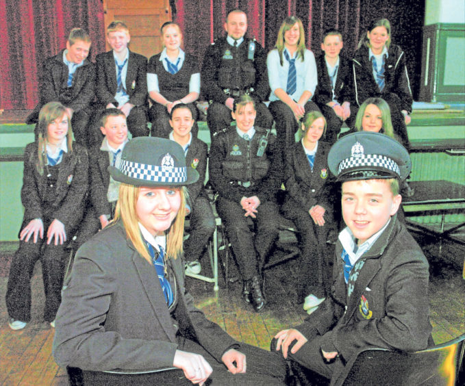 Jodie McDermott and Grant Ritchie try out police hats for size during a police visit to the tres bien: Pupils Rochelle Bowie and school in 2006