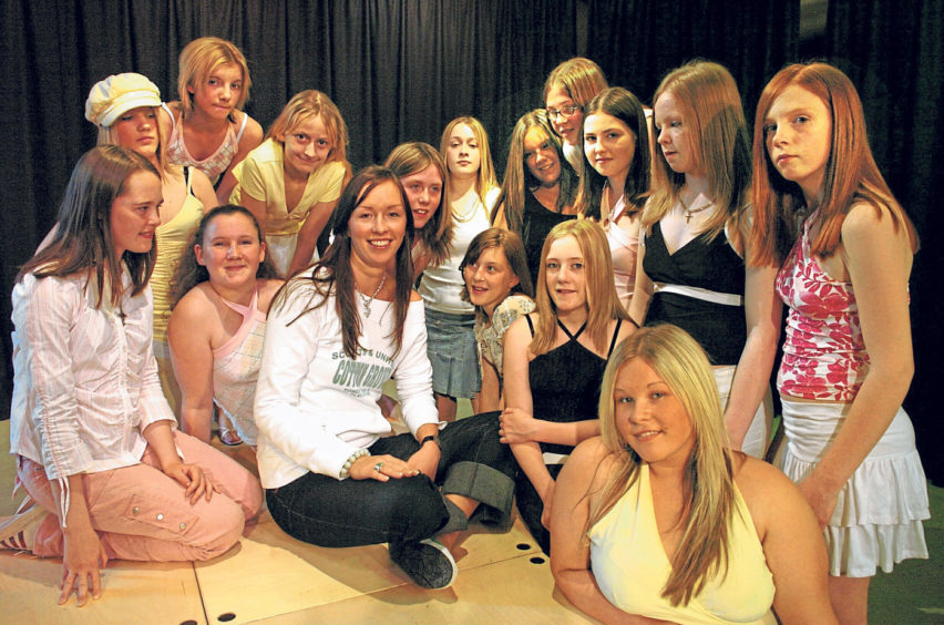 Model Sarah Cooper gives the girls some tips for a fashion show in 2004