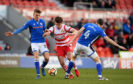 John Marquis of Doncaster is challenged by Jimmy McNulty of Rochdale during the FA Cup third round tie between Doncaster Rovers and Rochdale AFC at the Keepmoat Stadium