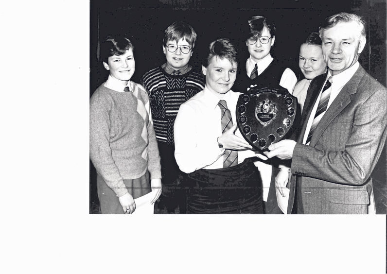 Kelly Ewen is presented with a shield by Stanley Flett after Torry pupils won the schools section of the Aberdeen and North-east Fund for the Blind flag day competition in 1986
