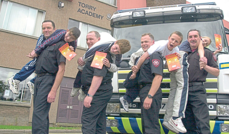 Altens A watch firefighters and Torry Academy pupils were handing out fire safety leaflets in 2001. From left, Hughie Anderson, 13, Michael Moir 13, Richard Melvin, 13, and Laura Winton, 13, held up by the firefighters