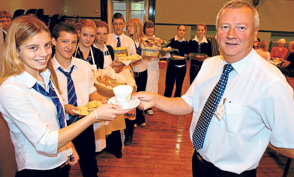 Pupil Stacey Donoghue serves head teacher Bob Skene at a coffee morning to raise funds for Macmillan Cancer Support in 2004