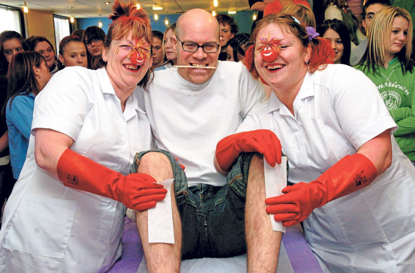 Maths teacher Craig Wilson gets his legs waxed by Denise Low, assistant cook, and Tracy Archibald, head cook, on Red Nose Day in 2005