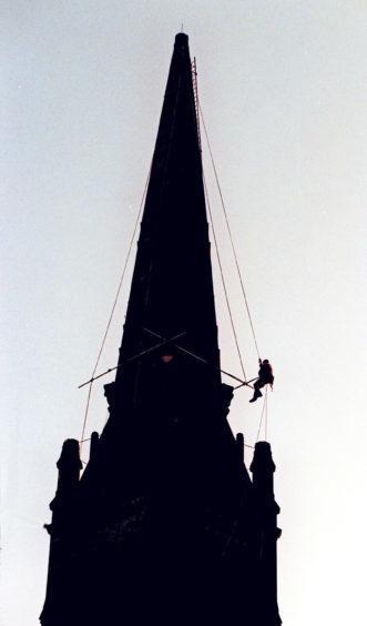 1998: A steeplejack carries out maintenance work at Langstane Kirk