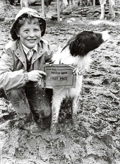 A smile from Alex Pirie, 9, as he and his dog Roy pose in a sea of mud