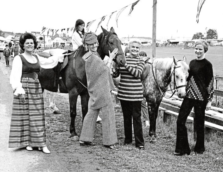 Turriff Show 1971-08-02 Fashion Parade (C)AJL Neg.No. 71-3995 - Scanned from print. Used P&J 03.08.1971. Ringing the fashion changes at Turriff: Modelling at Turriff Show fashion parade are (left to right) Alice Beattie, hostess evening gown; Kathleen Webster, Sir Walter Scott suit; Roselle Auld, black and gold trouser suit and Marianne Lumsden, cashmere trouser suit.