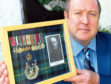 Graeme with his grandfather's miniature medals