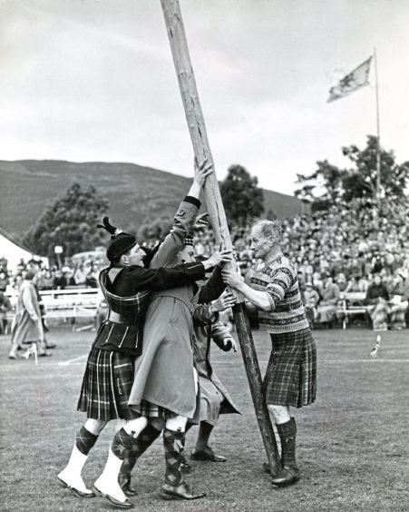 1953: Three men help raise the caber for Ian Grant, of Braemar