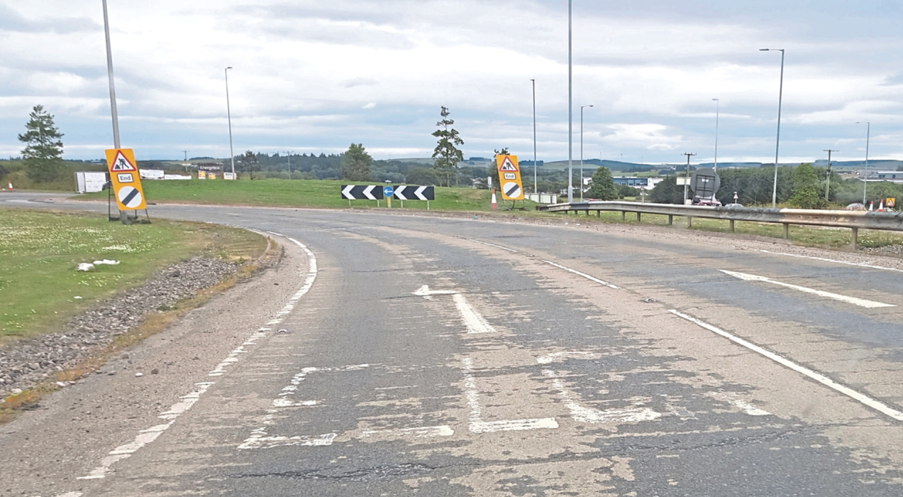 The faded road markings on the roundabout