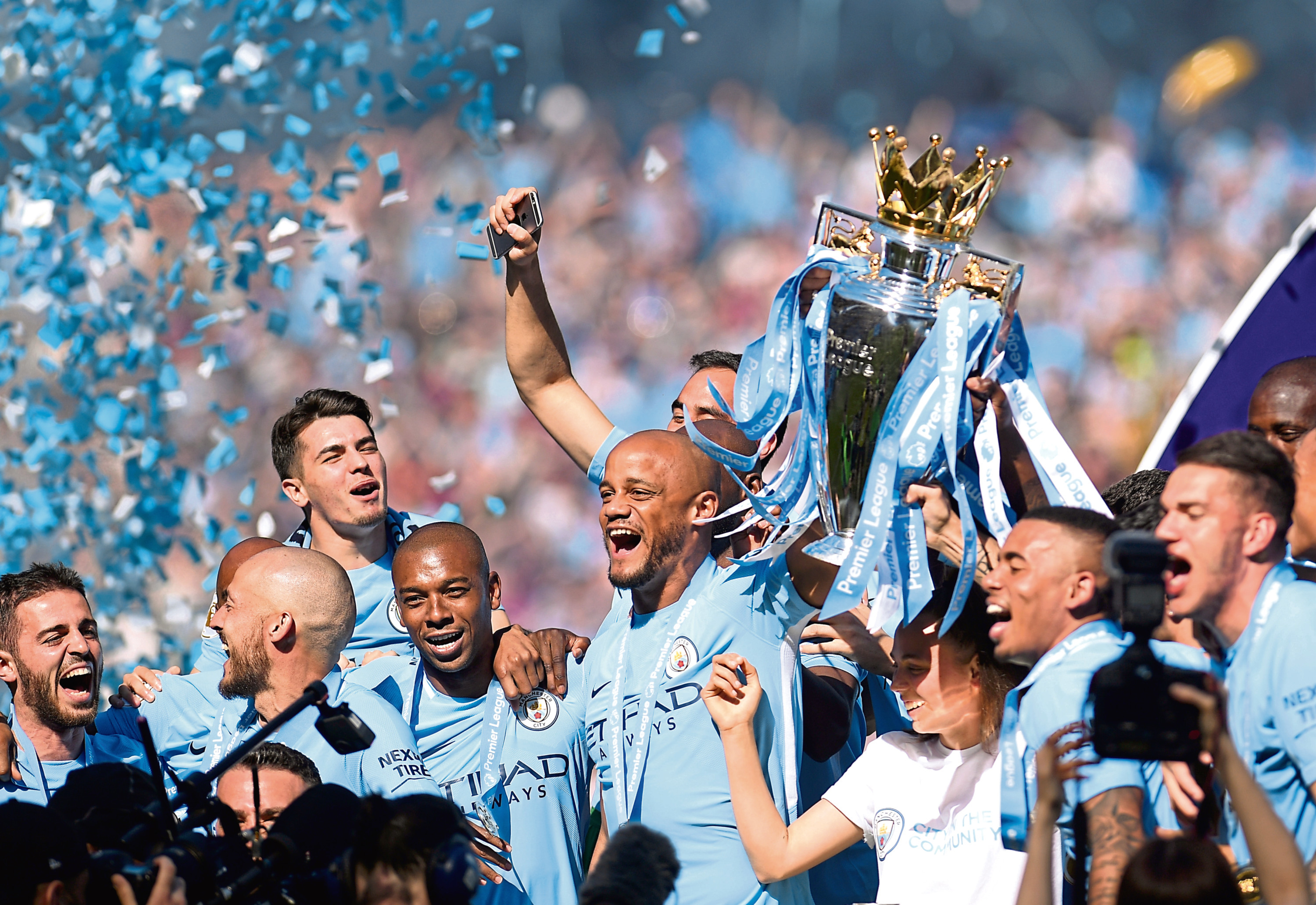 Triumphant Manchester City players hold the Premier League trophy aloft at the Etihad Stadium in May