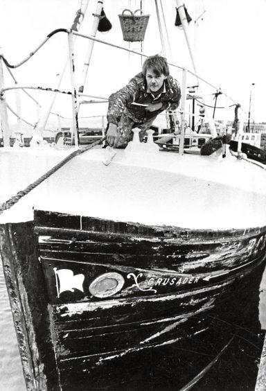 1985: Boat painter David Wielewski at work on the Crusader at Buckie Harbour