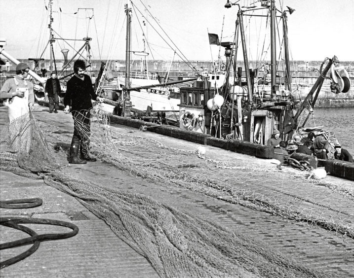 1975: Fishermen hard at work repairing nets in the sunshine at the harbour