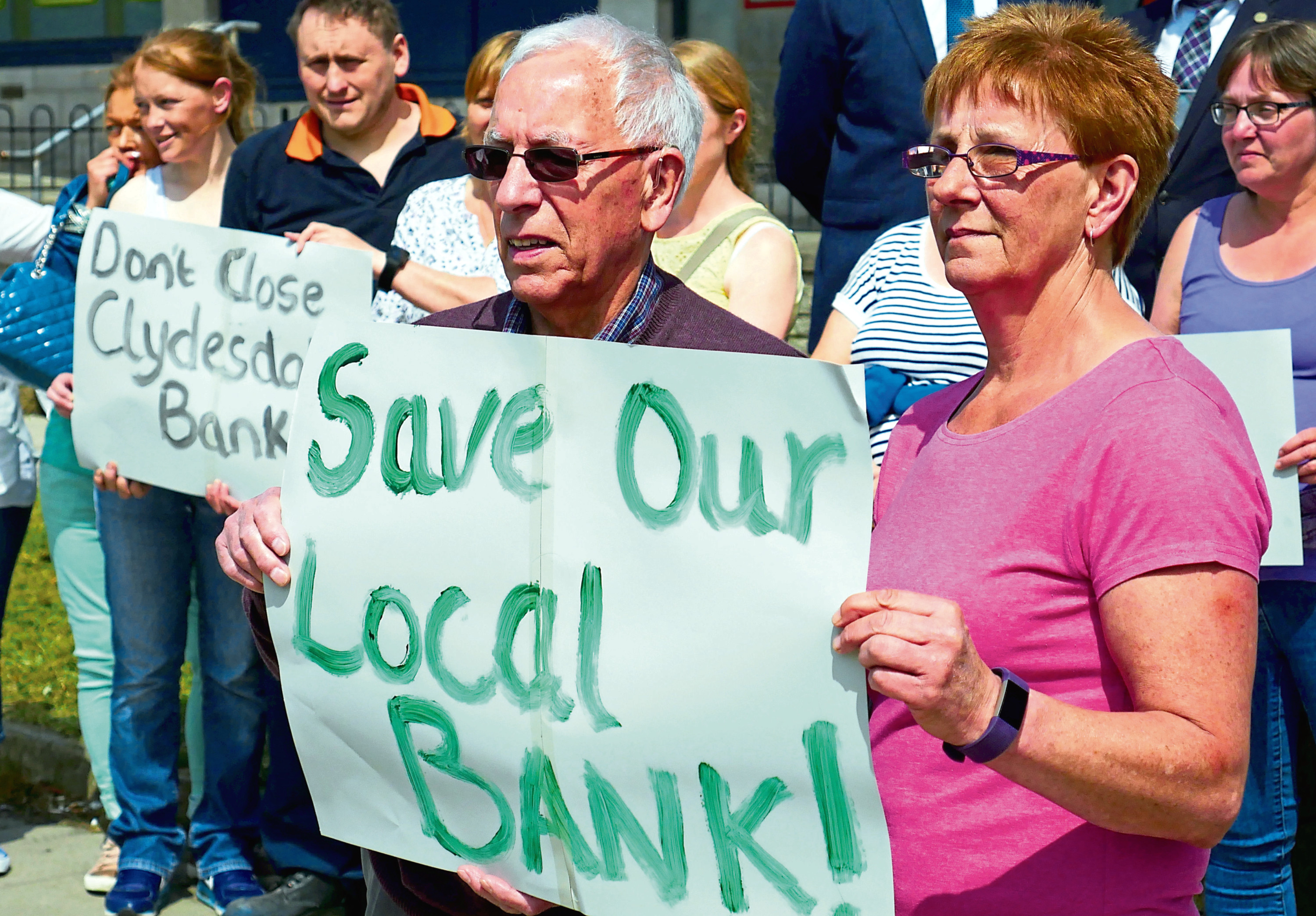 The Community show their protest at the closure of the Clydesdale Bank at Mastrick.     With Bert Donald chair of the Community Council (front holding banner with Elizabeth Barry)     Picture by Tom Ball    25-05-18