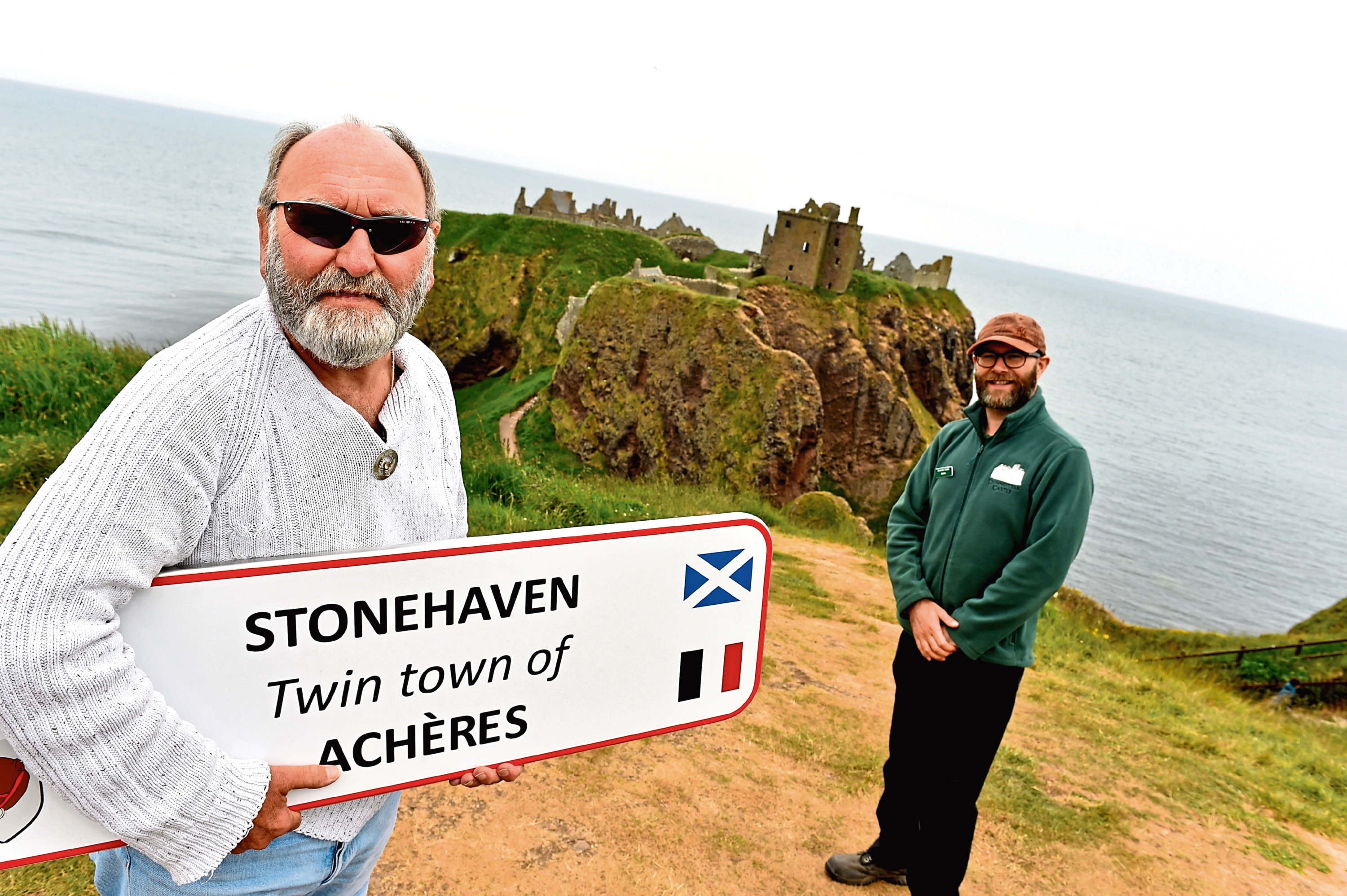 Phil Mills-Bishop, coordinator for Stonehaven Twinning Group with the Acheres sign.