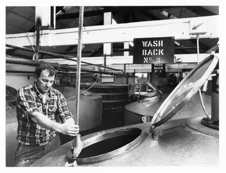 1979: Mashman Bob Clark dry dips a wash back to check on levels at Glen Garioch Distillery