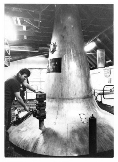 1979: Denis Kessack opens the air valve to discharge the still at Glen Garioch Distillery