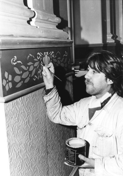 1986: Painter Douglas Styles touches up stencil work in the Music Hall auditorium
