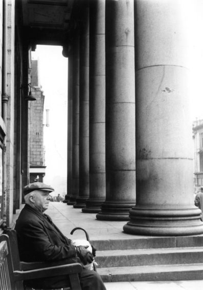 1961: A man stops for a rest on one of the seats outside the Music Hall