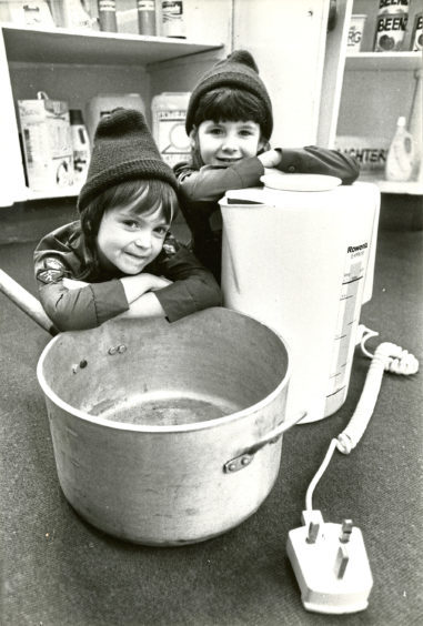 1989: Kelly Sutherland and Gillian Dingwall rest by a kettle and pan demonstrating a child's eye view of dangers in the kitchen