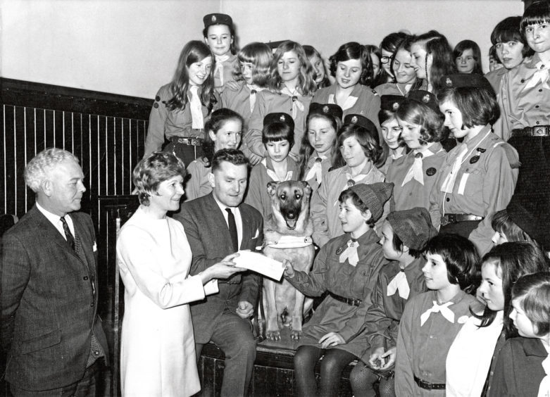 1970: Brownie Janet Stewart presents a cheque to Mr Alex Duguid of Guide Dogs for the Blind at Aberdeen's Beechgrove Church