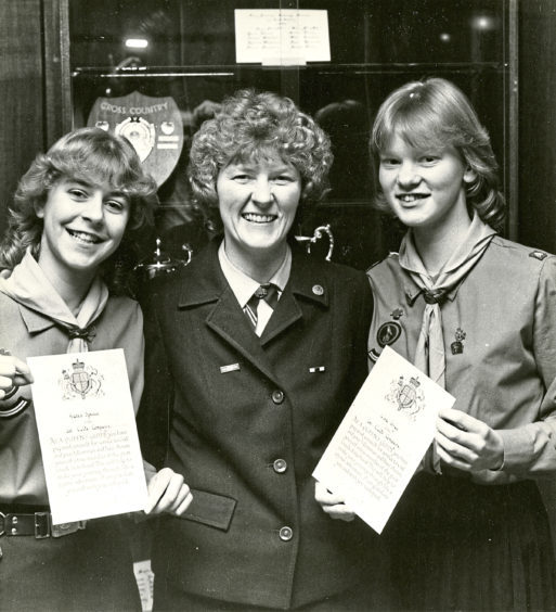 1984: Brownie Guider Dorothy Forbes of 1st Cults Pack presents awards to patrol leaders Karen Spence and Lisa Gray at Cults Academy hall
