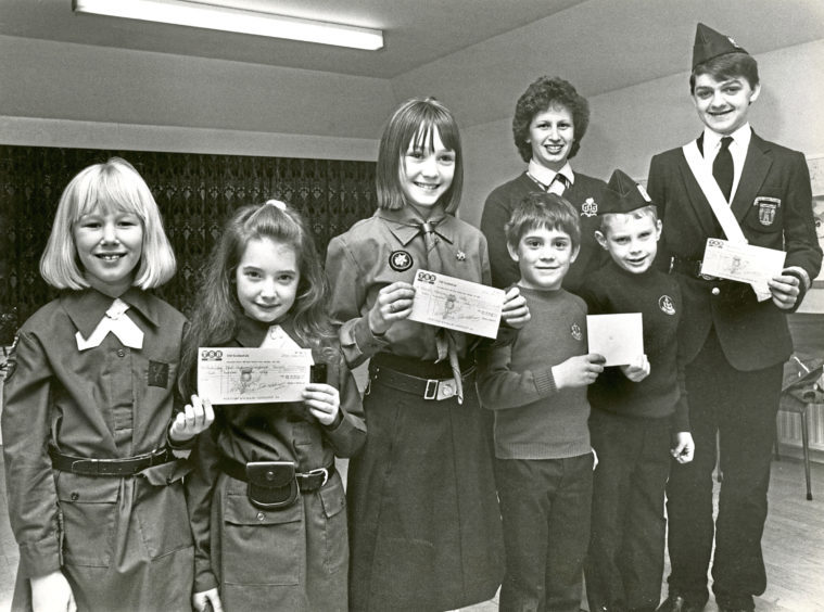 1987: Brownies Louisa Brown and Anna McGovan; Guide Isla Morrison and Boys' Brigade members Cameron Sharp, Andrew Harper and Keith Young were giving cheques to charity