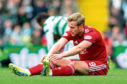 Aberdeen's James Wilson stretches out before being replaced in the match against Celtic.