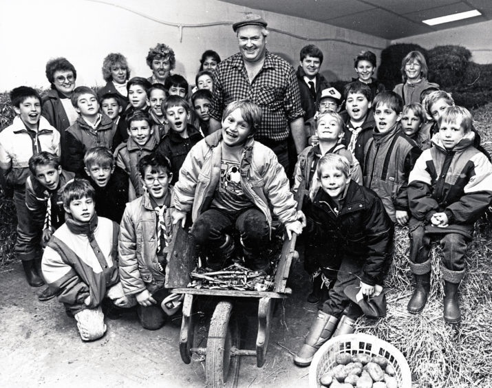 1987: Farm manager John Robertson with eight-year-old Ashley Painter and the American School Cub Scout pack during a visit to Easter Anguston Farm