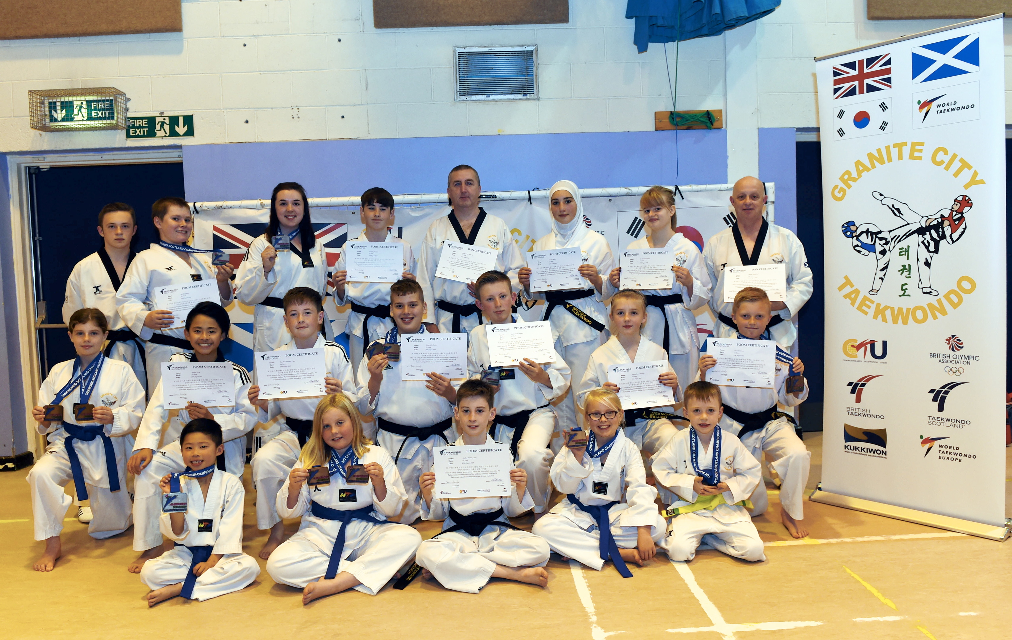 From left, top, assistant coach Aaron Reid; Ben Kaufmann, newly appointed black belt and silver medal for poomsae; assistant coach Shannon McNulty, silver medal in sparring; Conor Claire, newly appointed black belt; assistant coach Garry McNulty, achieved second dan black belt; Sawsan Basha, newly appointed black belt; Zoe Taylor, newly appointed black belt; Ally Reid, achieved second dan black belt  Middle, Louisa Smith, bronze medal for sparring and bronze medal for poomsae; Nathan Fong, achieved third Poom junior black belt; Ruadhan Claire, newly appointed black belt; Ethan Baxter, newly appointed black belt, silver medal for poomsae and silver for sparring; Lewis Campbell, newly appointed black belt and silver medal for poomsae; Saoirse McNulty, newly appointed black belt; Lucas Anderson, newly appointed black belt and bronze medal for poomsae  Bottom, Kayden Fong, silver medal for sparring; Anna-Mae Smith, bronze medal for poomsae and bronze medal for sparring; Seadna Claire, newly appointed black belt; Christina Stuart, bronze medal for poomsae; Ethan Thomson, bronze medal for sparring