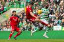 Aberdeen's Scott McKenna challenges Celtic's Odsonne Edouard .