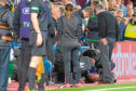 Hibernian manager Neil Lennon lies on the ground after appearing to be struct by an object from the crowd.