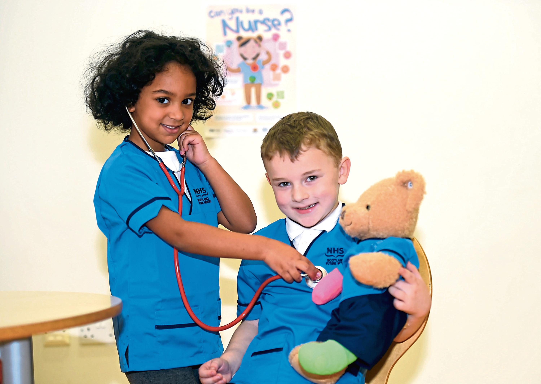 'Nurse' Farida Elgendi, 5, checks up on six-year old Riley Smith