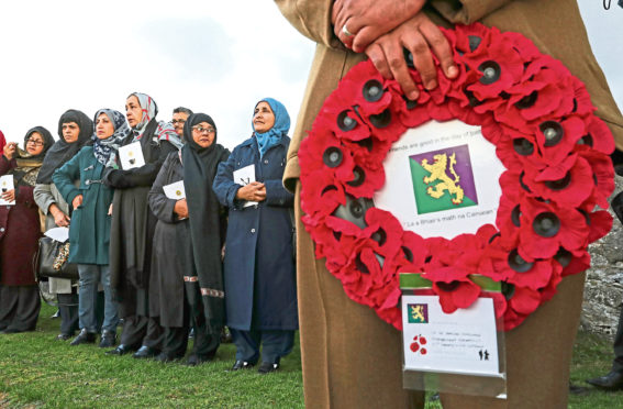 Women look on during Scotland's first multi-faith remembrance service for British Indian Army soldiers at Kingussie Cemetery in Badenoch. Andrew Milligan/PA Wire
