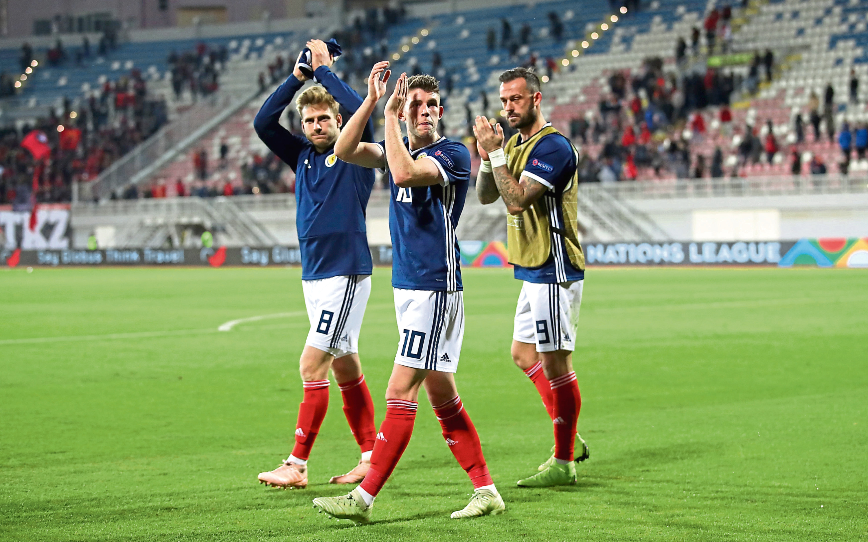 Scotland's Stuart Armstrong, Ryan Christie and Steven Fletcher applaud the fans after the final whistle.