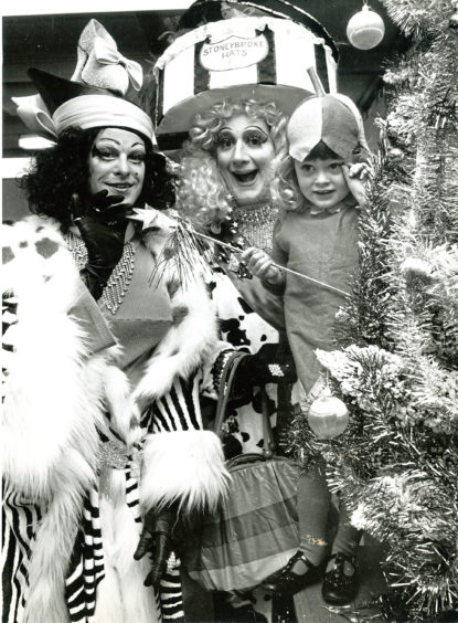 1987: Three-year-old Amy Donaldson caught the eye of Nigel Ellacot, left, and Peter Robbins from the cast of HMT's Cinderella at a fancy dress party