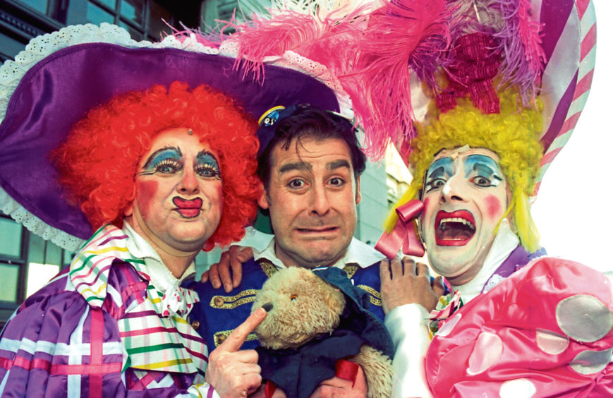 1996: The ugly sisters – Richard Pocock, left, and William Elliot – get their paws on Buttons, played by Andy Gray, in Cinderella