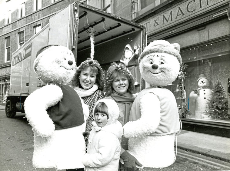 1987: Window dressers Denise Sproston, left, and Karen Presley were on hand to unload mechanical snowmen characters for the Esslemont and Macintosh Christmas display, and to introduce them to Dana Barclay, 4
