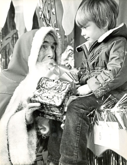 1983: Santa listens to some Christmas wishes from a young visitor to the Smurfs' Cave grotto in Aberdeen's Arnotts stor