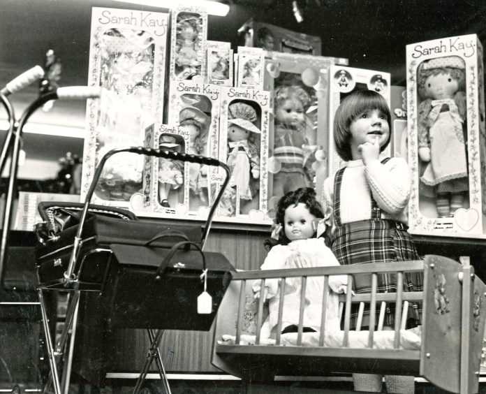 1979: A young girl eyes up the dolls on display in an Aberdeen shop