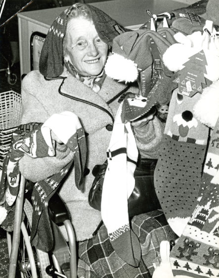 1988: Jean Thomson, of Turriff, gets all tangled up in Christmas stockings at the city's Marks and Spencer store on a shopping night for disabled people