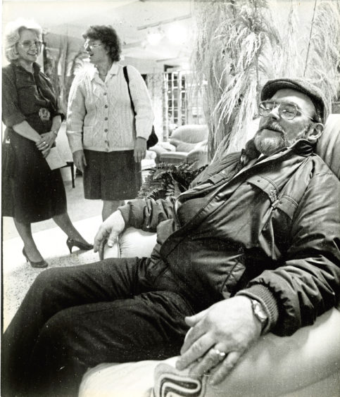 1985: After a hectic day's shopping, Alan McKay gratefully tests the comfort of an armchair in the House of Fraser furniture department