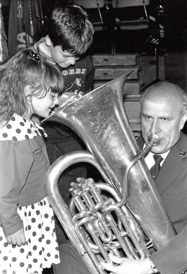 """1989: Wondering where all the noise is coming from are Frazer Shaw, 8, and his sister, Melissa, 4. Giving the """"lowdown"""" is tuba player George Payton"""