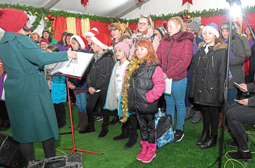 The VSA choir performing at the Marischal College Quad as part of the Christmas Village activities