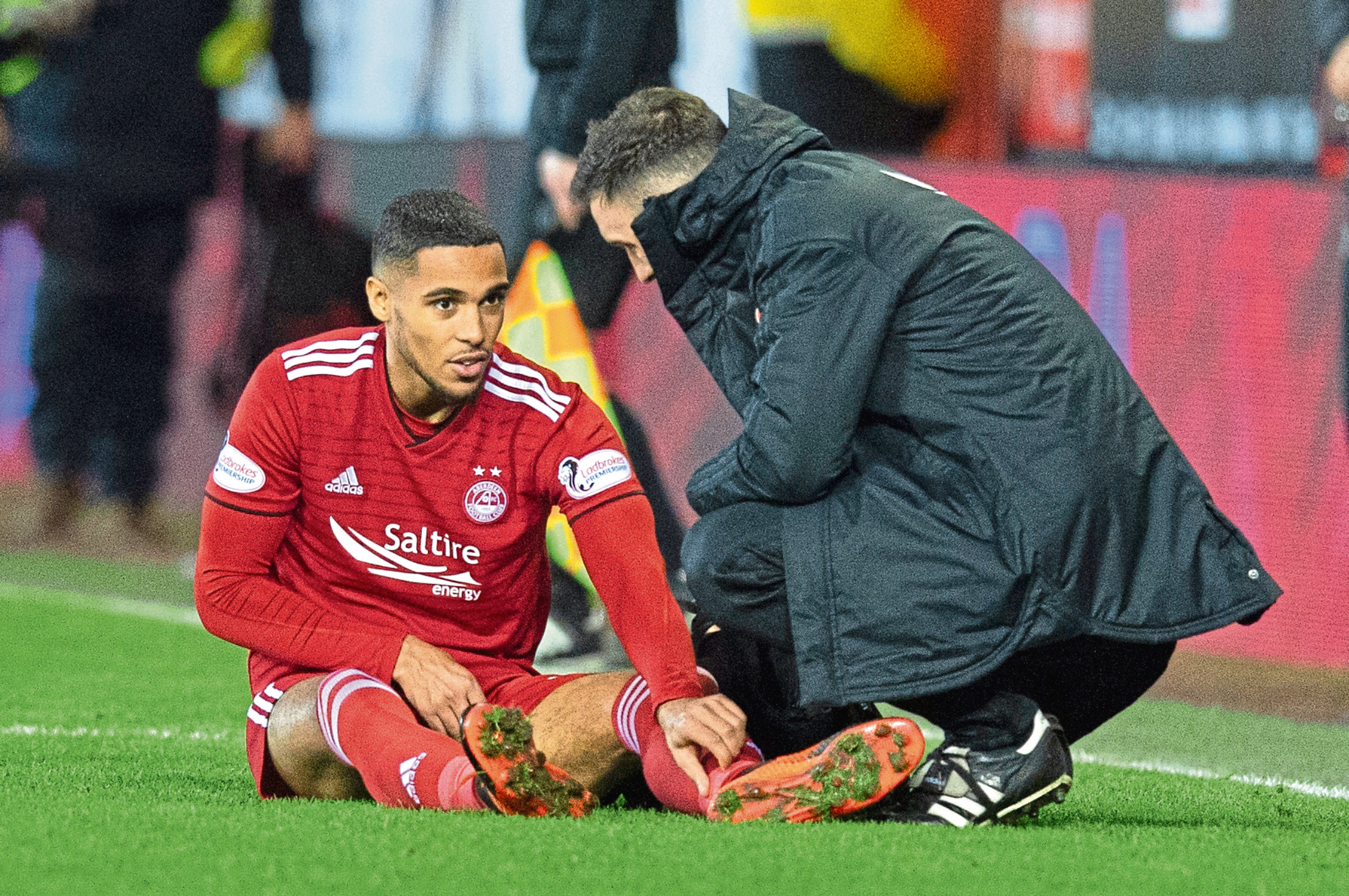 Aberdeen's Max Lowe receives treatment for an injury.