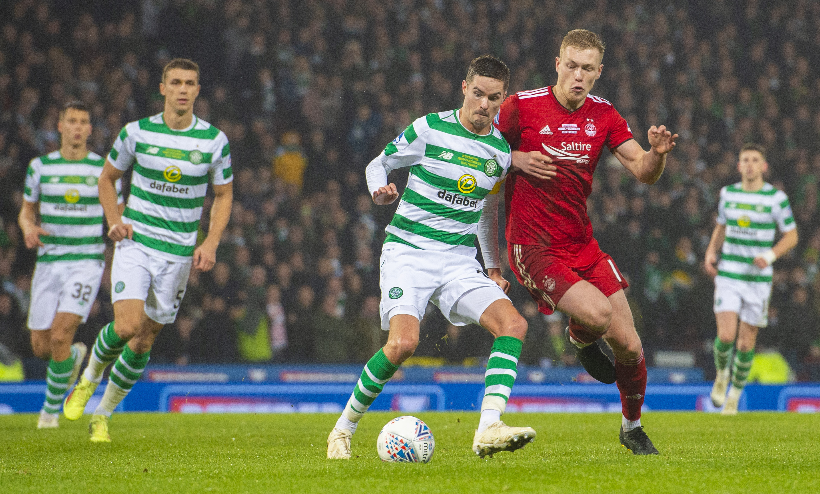Celtic's Mikael Lustig, left, holds off Aberdeen's Sam Cosgrove.