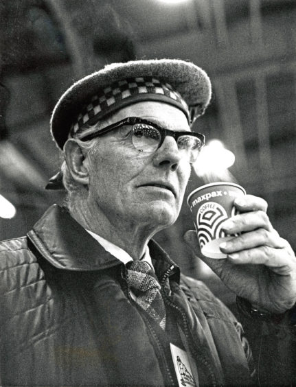 1976: Umpire John Carmichael takes precautions against the cold with a warming drink