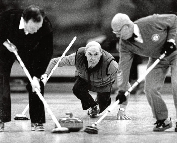 1989: Aberdeen skip Sandy Shand pays close attention to the weight of his stone as his teammates wait for the call to begin sweeping during the RCC rink championship